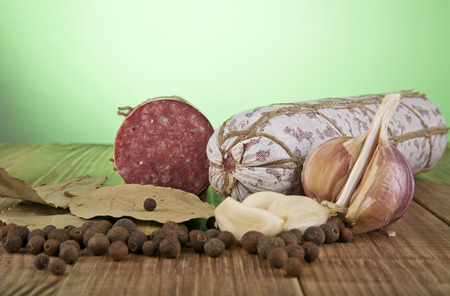 salame: salame, garlic and laurel leaves on a green background Stock Photo