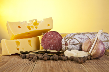 longaniza: salame, garlic and laurel leaves on a yellow background Stock Photo