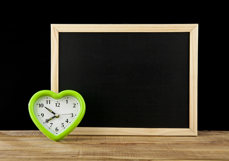 impatient: green clock by a heart and board for inscription on a black background