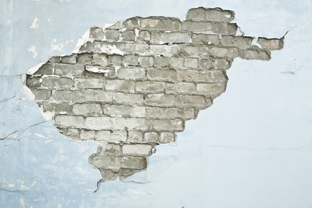 cracked wall: cracked brick wall blue background Stock Photo