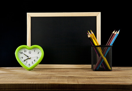 impatient: green clock by a heart, board for inscription and pencils on a black background Stock Photo