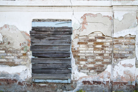 boarded up: old wall with boarded up windows in an old empty house