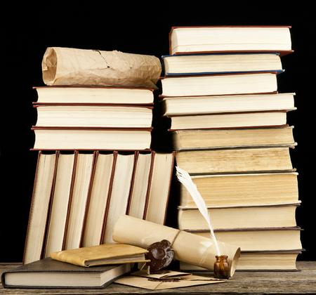 pluma de escribir antigua: libros antiguos sobre un fondo negro