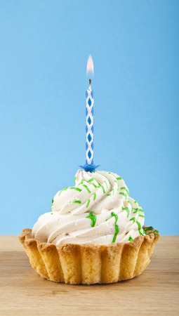 butter icing: cake with candle on blue background