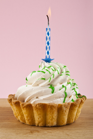 plain background: cake with candle on pink background