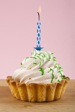 pink bow: torta con la vela en el fondo de color rosa Foto de archivo