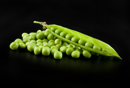 snap bean: green peas on a black background closeup