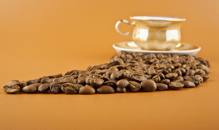 Cup of hot coffee and coffee beans on brown background closeup