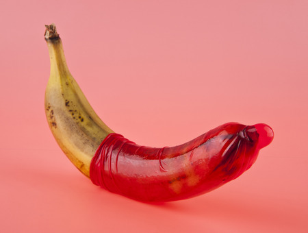 banana and red condom on a pink background