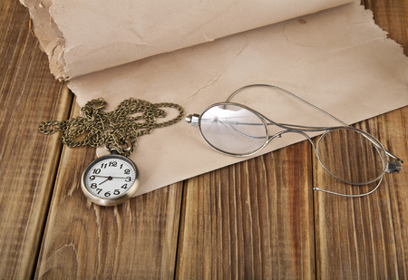 watches, old glasses and old paper on a wooden table Archivio Fotografico