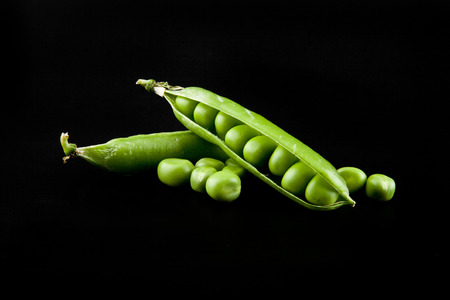 Green peas on a black background