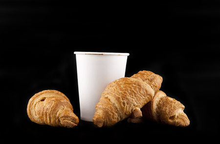 Paper glass with coffee and croissants on a black background