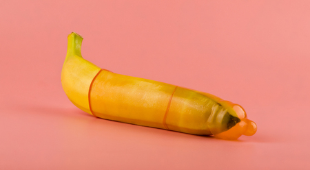 Banana in a condom on a pink background
