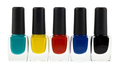 Colored bottles with nail polish isolated on white background close up.