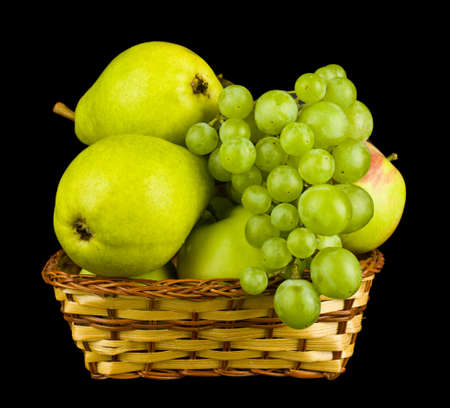 Fruit apples, pears and grapes in a basket isolated on a black background close-up. Healthy food concept, vegetarian food.