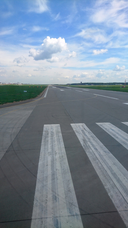 Airport runway and blue cloudy sky