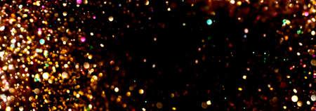 Golden sparkling confetti bokeh on a black banner background