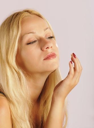 Pretty blond girl applying moisturizer photo