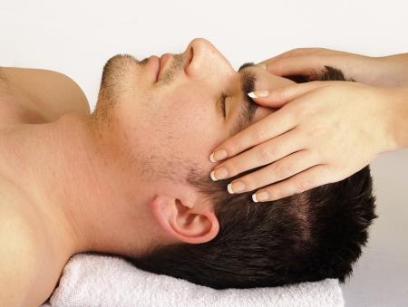 masajes faciales: Hombre recibiendo un masaje de cara Foto de archivo