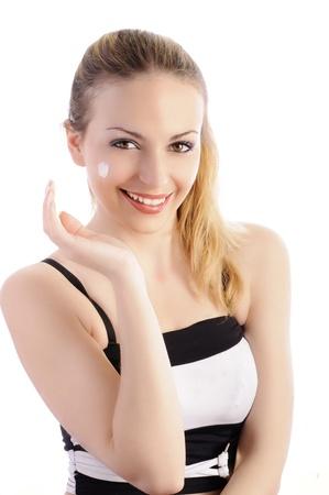 Pretty blond girl applying moisturizer