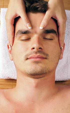masajes faciales: Hombre recibiendo un masaje facial Foto de archivo