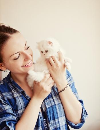 Girl holding Persian kitten
