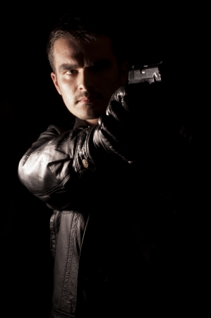 hitman: Young man holding a gun Stock Photo
