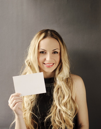 Girl holding blank piece of paper Stock Photo - 27560017