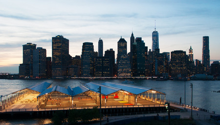 bowery: New York City skyline seen from Brooklyn Heights Promenade at sunset, lights