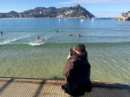 basque country: A girl sitting on the pier of Donostia-San Sebastian, Basque Country, City, Spain. The La Concha beach, panoramic view. 28012017