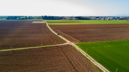 unexplored: A jeep crossing a country road, off-road aerial view of a car traveling a dirt road through the fields. Traveling, spend holidays in nature