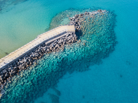 Aerial view of a pier with rocks and rocks on the sea. Pier of Pizzo Calabro, panoramic view from above. Summer sea and tourism on the Calabrian coast of Southern Italy. Calabria, Italy
