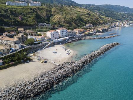 Aerial view of a beach with canoes, boats and umbrellas. Pier of Pizzo Calabro, panoramic view from above. Summer sea and tourism on the Calabrian coast of Southern Italy. Calabria, Italy