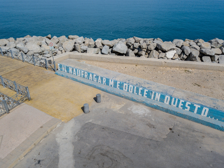 Pier and writing on the jersey barrier: and the naufragar is sweet in this sea, aerial view. It is from poetry: The infinity of Giacomo Leopardi. A famous poets verse