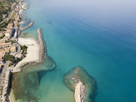 Aerial view of a beach and a pier with canoes, boats and umbrellas. Pizzo Calabro, Calabria, Italy