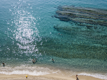 nuances: Aerial view of the rocks on the sea. Overview of seabed seen from above, transparent water. Swimmers, bathers floating on the water