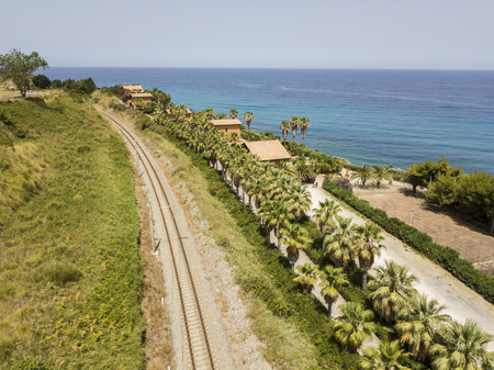 Train tracks crossing the coast with sea views, departing tourist routes. Aerial view
