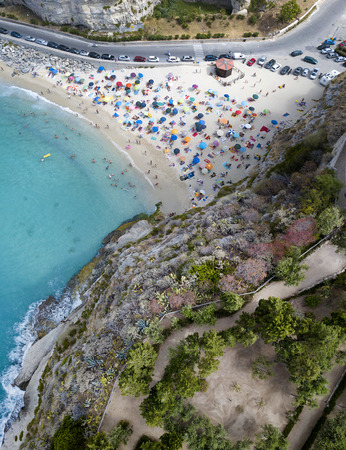 Aerial view of a beach with umbrellas and bathers. Promontory of the Sanctuary of Santa Maria dellIsola, Tropea, Calabria, Italy