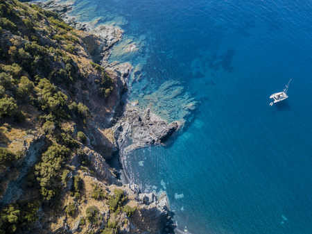 Aerial view of a cliff overlooking the sea and a moored catamaran, boat. Cap Corse Peninsula, Corsica. Coastline. france