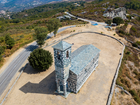 Aerial view of the church of San Michele de Murato, bell tower and aps. Surrounded by a square with trees. Northern Corsica. france Stock Photo