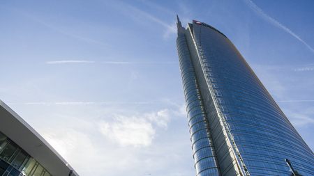 Unicredit tower seen from Gae Aulenti square, people walking. Italys tallest skyscraper building