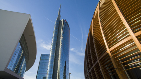 Unicredit tower and Unicredit pavilion seen from Gae Aulenti square, people walking. Italys tallest skyscraper building