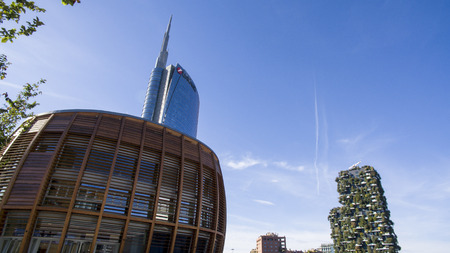 Unicredit tower and Unicredit pavilion seen from Gae Aulenti square, people walking. Italys tallest skyscraper building. On the right you can see the vertical forest Editorial