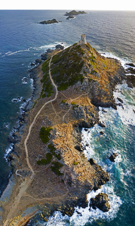walking paths: Aerial view of the Bloods Islands and the Parata Tower, the Genoese tower built in 1608, Corsica. France. Sunset over the sea on the dark red porphyry islands Stock Photo