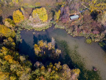 Nature and landscape: aerial view of forest and lakes, autumn leaves, foliage, greenery and trees in a wilderness landscape. Nature reserve and sightseeing hut