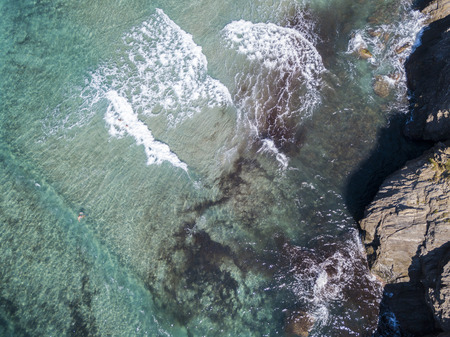 Aerial view of the rocks on the sea. Overview of seabed seen from above, transparent water. Swimmers, bathers floating on the water.