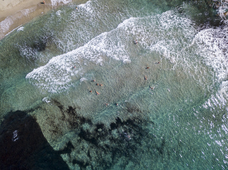 Aerial view of the rocks on the sea. Overview of seabed seen from above, transparent water. Swimmers, bathers floating on the water
