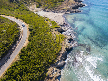 Aerial view of the coast of Corsica, winding roads and coves with crystalline sea. Cap Corse Peninsula, Corsica. Coastline. Anse dAliso. Gulf of Aliso. france