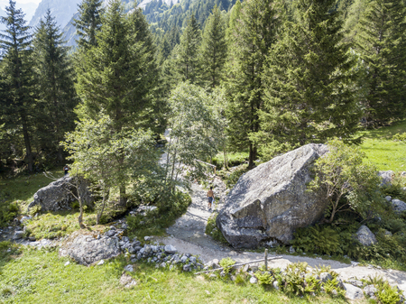 People seen from above on a mountain path. Trekking and hiking. People crossing a forest with backpackers