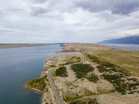Aerial view of Croatia, winding roads and crystal clear sea. Coast of the island of Pag 版權商用圖片